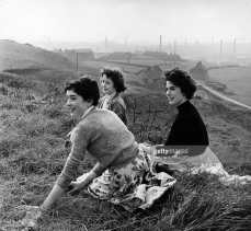 A group of teenage girls sitting on a hillside above an industrial town 1957 © Bert Hardy
