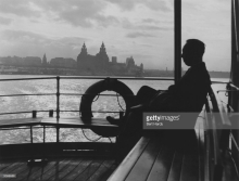 A man sitting on the Mersey ferry with the Liver building in the background. Original Publication Picture Post - 7897 - Liverpool Ferries - unpub © Bert Hardy