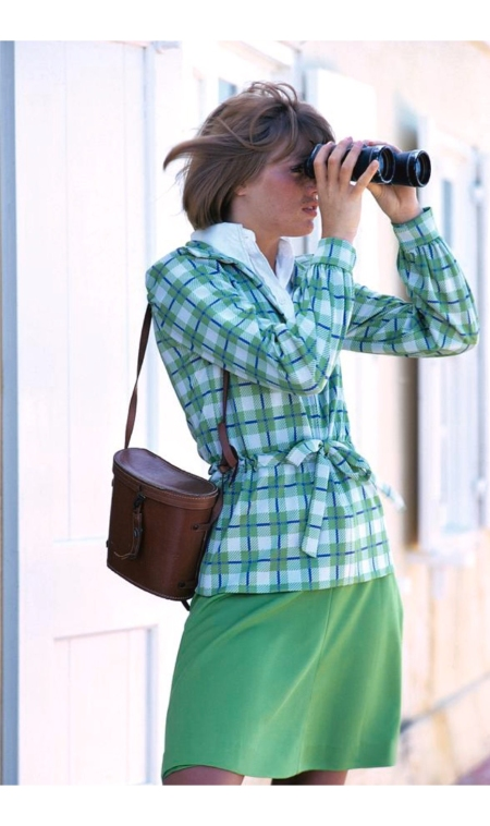 A model wearing blue and green plaid jacket holding binoculars Glam march 1973 © William Connors