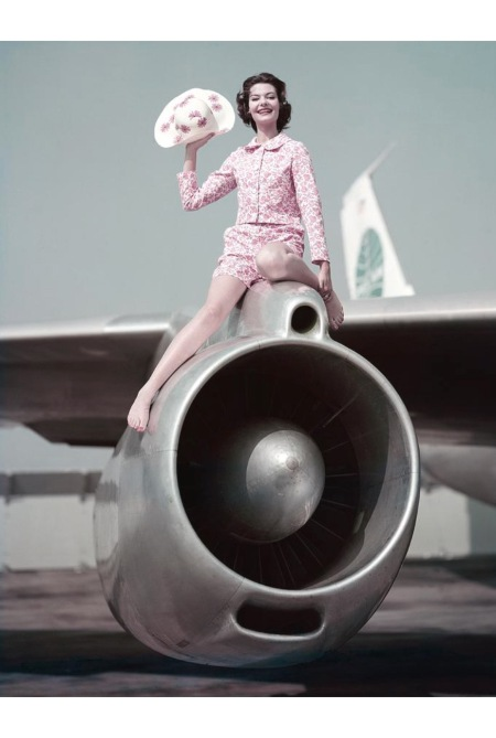 A model wearing pink sitting on an airplane engine Jan 1959