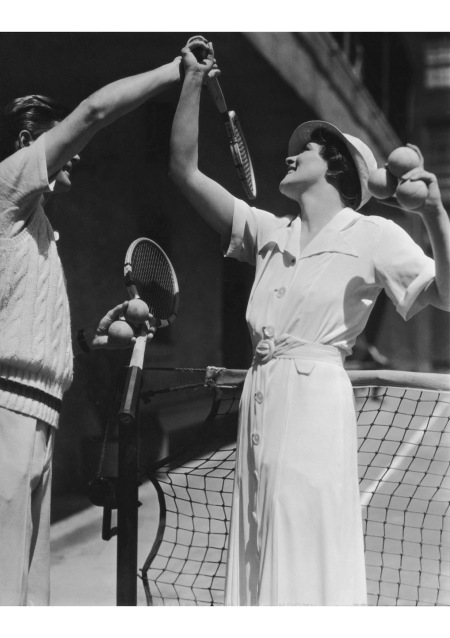 A third example of the long-placketed tennis dress, antecedent to the everyday shirt dress, on the court with a game instructor this is silent-screen actress and femme fatale Irene Rich,