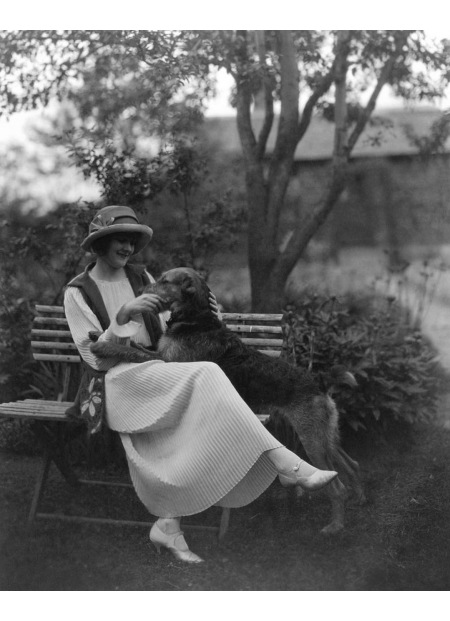 American actress Jeanne Eagels sitting down on a park bench with a dog Vanity Fair 1923 © maurice Goldberg