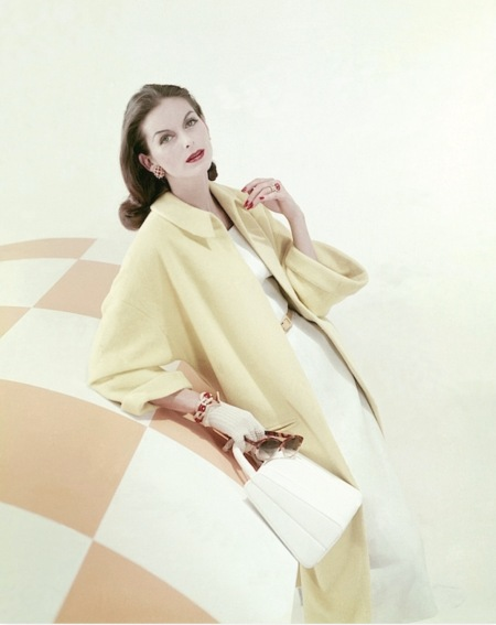 Anne St. Marie in yellow wool fleece coat by Originala over a white linen dress by Ben Barrack, coral jewelry by David Webb, cover by Frances McLaughlin, Vogue, January 1956 b
