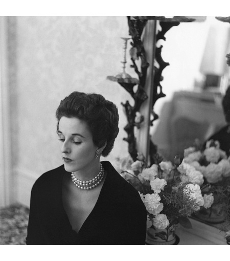 Babe Paley looking elegant in a pearl necklace and diamond earrings while standing next to a mantle © Frances Mclaughlin-Gill
