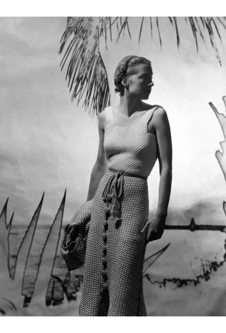 Being able to move freely on the beach was not confined to swimwear a knit cover-up from 1934 by Hermès, a precursor to the knit maxi dress of later decades, is shown among the palms in