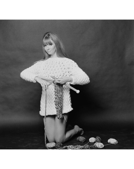 Carol Christopher models a long white knitted sweater called 'Long Island', whilst knitting with maxi-pins (oversize knitting needles), UK, 2nd November 1967