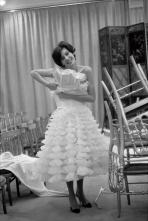 Chanel model, Mimi d'Arcangues holds up a tiered, ruffled dress in the salon 1959 © WillyRizzo