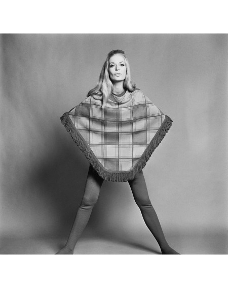 Charlotte Louise models a pink and purple checked woollen poncho over purple tights, UK, 15th September 1967