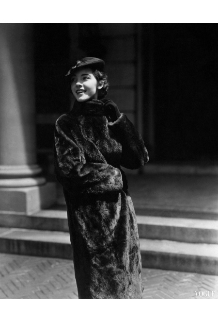 College woman wearing a full-length nutria swagger coat with felt beret Vogue Aug 1934 © Lusha Nelson