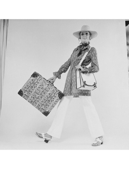 JJ models a pair of white trousers and hat with a suitcase in a reptile print, UK, 29th June 1970
