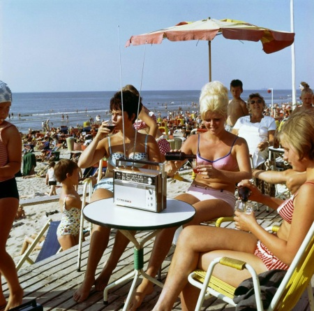 Lady with transistor radio on terrace at beach tent b