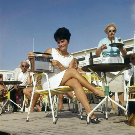 Lady with transistor radio on terrace at beach tent