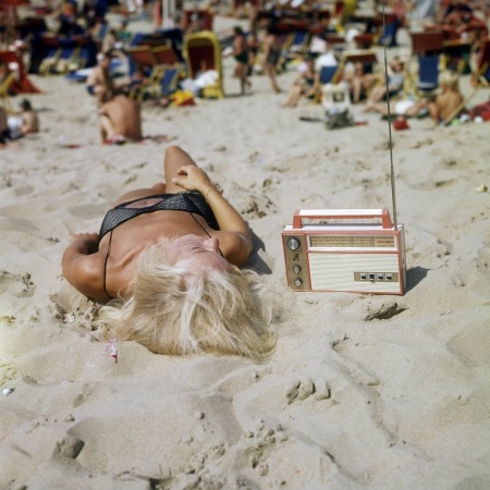 Lady with transistor radio on the beach © Nico van der Stam