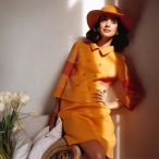 Marisa Berenson wearing an orange skirt suit and hat by Mila Schon march 1968