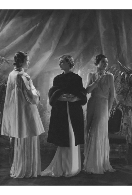 Mlle. Koopman wearing a satin wrap with sable cuffs flanked by two models wearing dresses designed by Augustabernard april 1933 © Huene