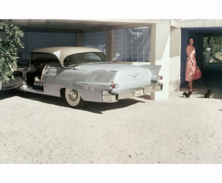 Model in pink belted dress by Claire McCardel Pale Blue Cadillac Eldorado Seville in Garage Dec 1955 © Horst P.Horst