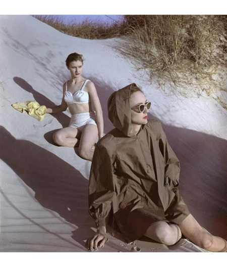 Model Kitty Lou Smith wearing a bikini and Susan Gresham wearing a coat on sand dunes May 1947 © Luis Lemus