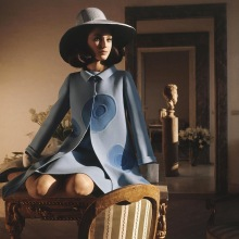 Model sitting on a desk wearing a double-faced Nattier wool coat and straw hat by Mila Schon march 1968