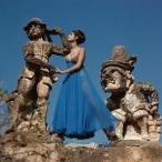 Model standing between statues at the Villa Palagonia, Bagheria, Sicily dec 1967
