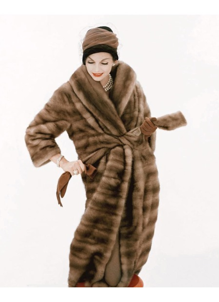 Model wearing a belted fur coat and hat by Lilly Dache Oct 1958