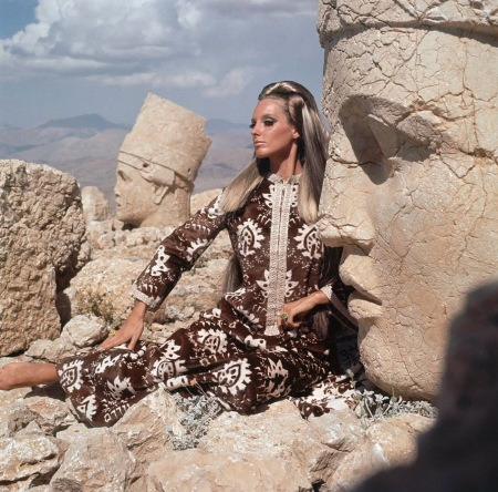 Model wearing a brown and white Persian print jibba by Chombert sitting on Turkish ruins dec 1966