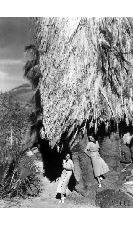 Models wearing a belted gray linen dress; and a two-piece fringed silk crepe belted dress, standing under a large palm tree in Palm Springs. horst-p-horst-vogue-january-1936