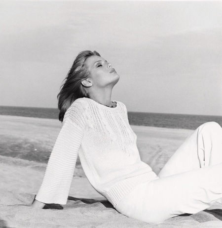 Patti Hansen on beach, leaning back, wearing a white cable-knit cotton sweater with matching pants by Rowan for Jones New York nov 1975