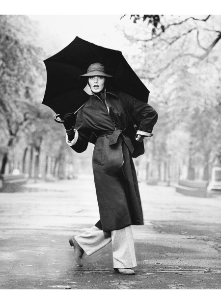 Rene Russo wearing a coat and trousers, carrying an umbrella July 1974 © Francesco Scavullo