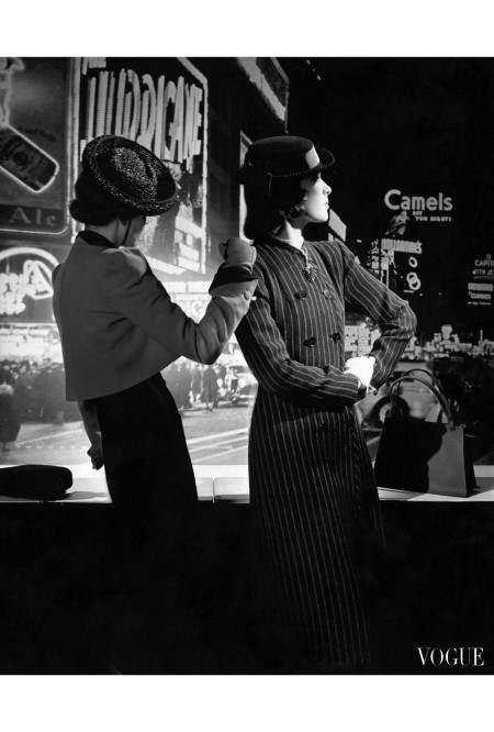 Two models on 42nd Street New York City at night, wearing (from the left) a bolero, slim dress and a straw Breton hat with chin band; a long, double-breasted, pinstriped suit jacket and