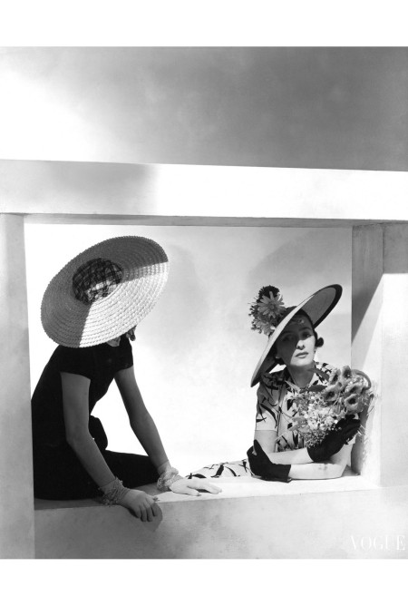 Two models sitting in a window hat John Frederics horst-p-horst-vogue-may-1937
