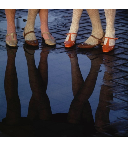 Women's shoes and legs reflect in puddle