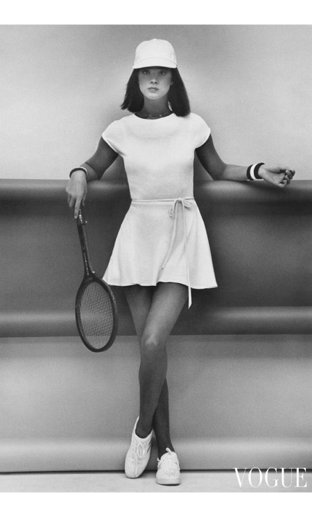 A model holding a tennis racquet, wearing a wrap dress and cap Vogue Mat 1977 © Albert Watson