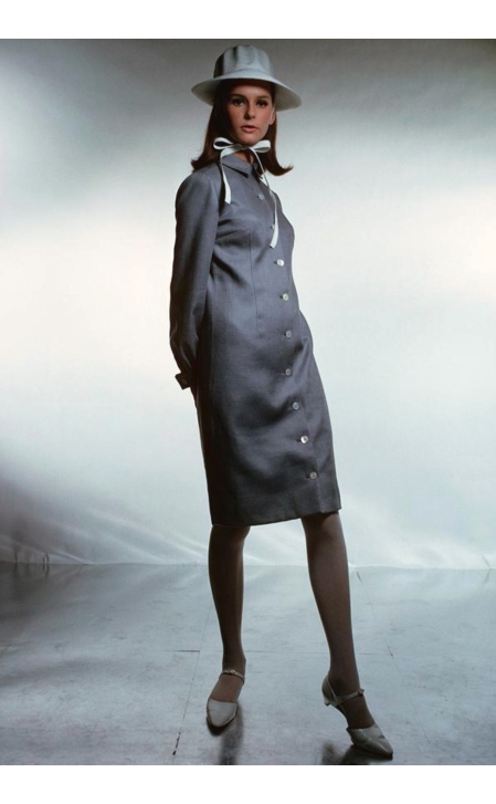 A model wearing a grey dress by Anne Fogarty and a hat march 1965