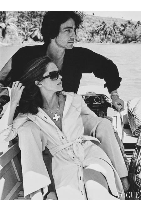 Actors Lois Chiles and Sam Waterston sitting in the back of a boat on the Rio Chavon, La Romana, Dominican Republic; she's wearing a shirtdress by Bill Smith for the Skip II Collections