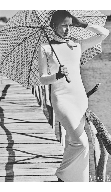Actress and model Lois Chiles wearing long white tee-shirt dress, with scarf at neck; holding parasol and standing beside bridge railing in La Romana, Dominican Republic Vogue June 1973