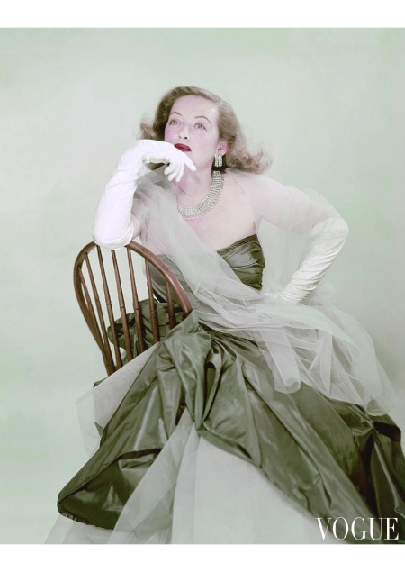 Bette Davis wearing a strapless blue-green evening dress with a sheer stole, long white gloves, diamond necklace and earrings Vogue May 1951 © Erwin Blumenfeld