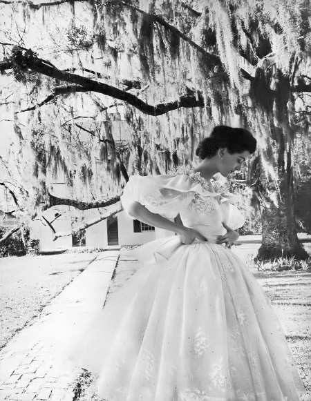 Carmen in short evening dress of white organdy sprinkled with brilliants, the underskirt and shoulder wreath are pink, by Howard Greer, photo by Gleb Derujinsky in Natchez, Mississippi,