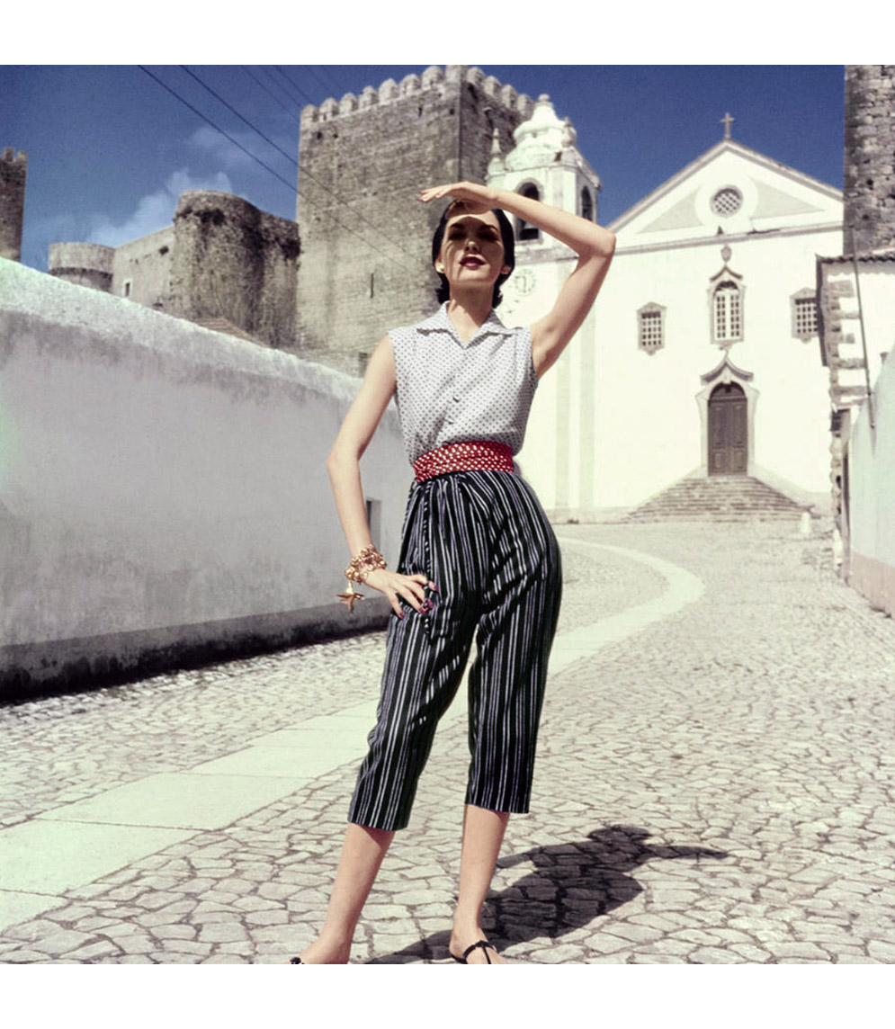 Cherry Nelms in Portugal, shading her eyes from the sun, wearing Peter Pan pique shirt and pinstriped, twill, capri pants, tapered from a draw-string top Vogue June 1952 © Henry Clarke
