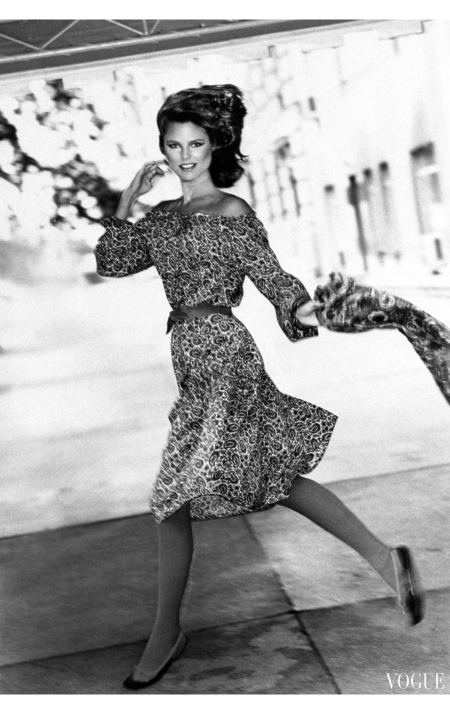 Christie Brinkley running on a sidewalk, wearing a paisley print dress belted at waist, by Leslie Fay, with drawstring neck and flounced skirt, carrying matching scarf Vogue Sept 1977 ©
