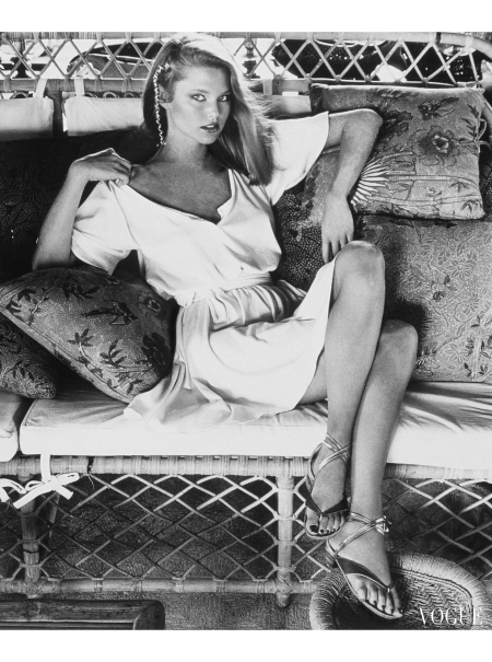 Christie Brinkley sitting with crossed legs on a wicker couch with pillows, and wearing a short ivory T-shirt dress by Callaghan. Vogue April 1977 © Kourken Pakchanian