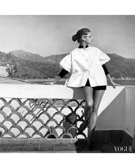Fiona Campbell-Walter in white twill beach cover-up with black nit cuffs and collar worn with black corduroy shorts by Reel-Poise, photo by Henry Clarke in Palermo harbor, Sicily, Vogue,