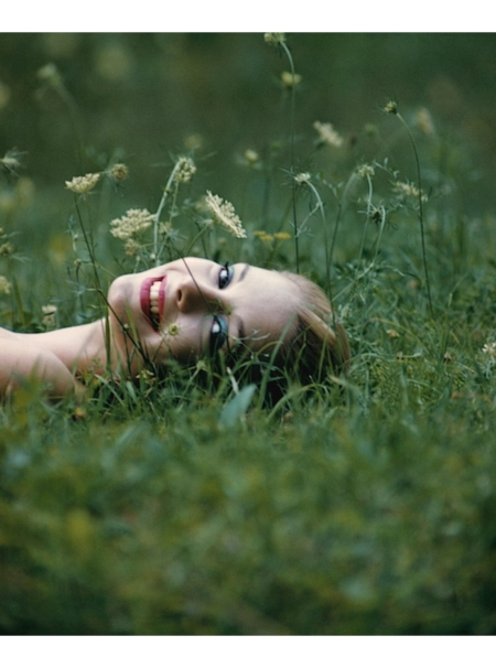 Gretchen Harris lying in a field of grass july 1957