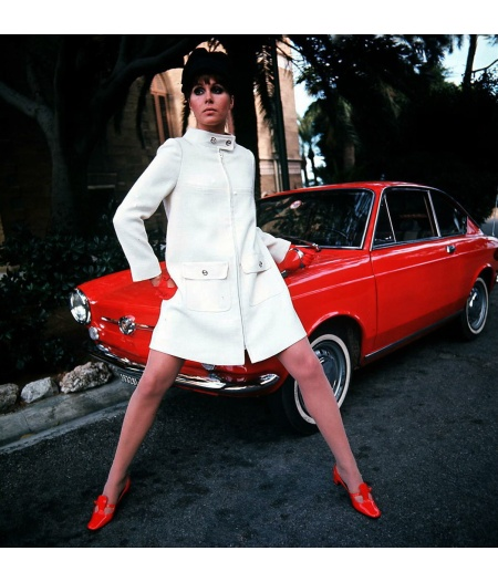 Joanna Lumley poses by a red Fiat 850 Coupé as she models a white coat worn with red shoes and matching gloves, 1968. (Photo by Popperfoto:Getty Images)