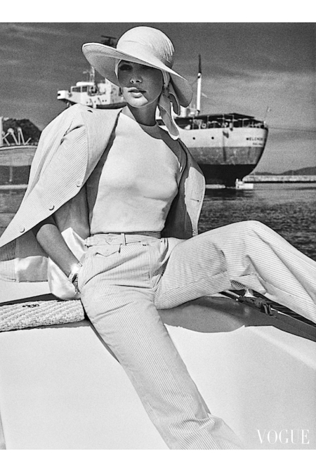 Model and actress Lois Chiles wearing striped seersucker pantsuit by Ralph Lauren, with headwrap and Panama-style hat, sitting dockside in Manzanillo, Mexico with sea and oil tanker in b