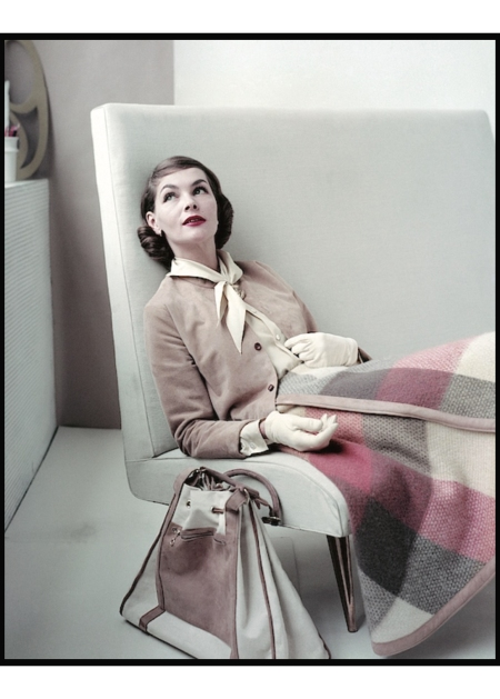 Model sitting in chair wearing plaid skirt, suede jacket, blouse and gloves by Glen of Michigan Glamour August 1955
