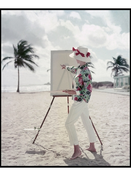 Model standing on a beach in front of an easel, in a patterned shirt and pants by Queen Casuals and a Sally V. straw hat Glamour April 1960 © Frances McLaughlin-Gill