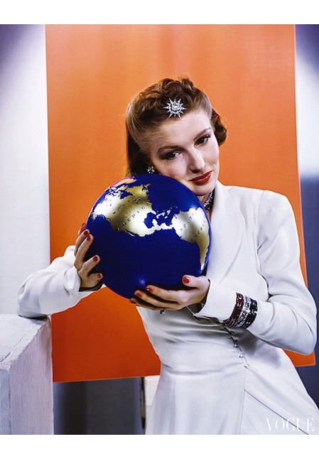 Model Susann Shaw in jewelry and white top, holding blue-and-gold globe with North and South America labeled on it Vogue feb 1940 © Edward Steichen