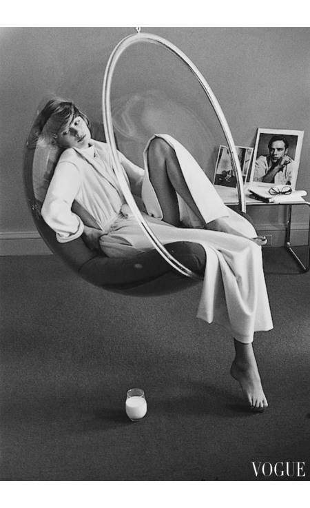 Model wearing a Stella Fagin dressing gown sitting in a hanging chair Vogue May 1972