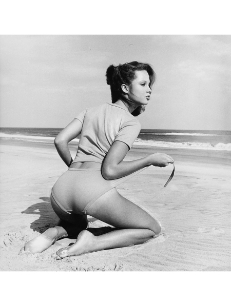 Models Rosie Vela & Dalila Di Lazzaro seen from the back, kneeling on a beach, wearing a T-shirt and a wrap-front panty in cotton knit by Jeb Manning Vogue July 1975 © Francesco Scavull