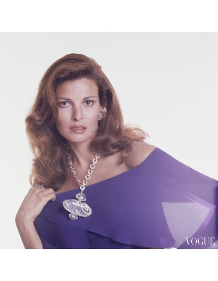 Raquel Welch wearing crystal pendant wrapped in gold and diamonds hanging on crystal link chain with matching earrings by Gerard, off the shoulder violet silk crepe dress by Pierre Cardi